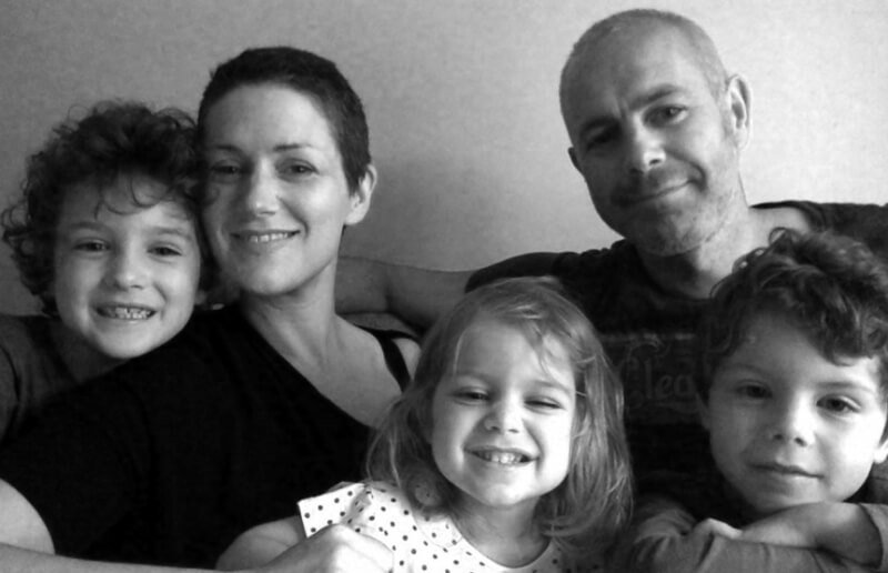 Black and white image of a family (a woman and man, their two older boys and youngest, a daughter, all smiling.